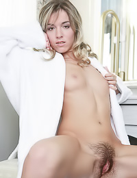 Lusty Sofy A takes her white gown off and unveils her messy hairy cunt on her white bed.