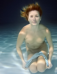 Underwater siren with red hair big boobs and sexy ass takes off all of her clothes and swims.