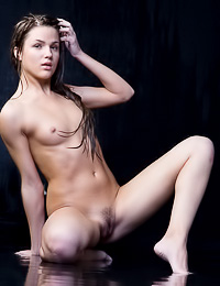 Cute Aurika B wanted to be surounded with wather and black wall while posing naked and wet.