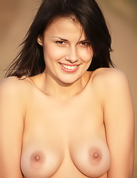 Big breasted brunette cuttie Emanuel A takes her clothes off on the field and shows her rack.