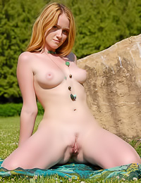 Cute and sexy redhead babe Alexa C poses on the green field and shows her ginger twat.