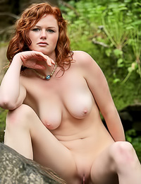 Big breasted redhead model Elena Marie takes her clothes off in the river and shows her jugs.