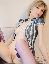 Cute and sexy blonde chick Janna A shows us her perky breasts as she teases in purple stockings.