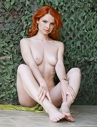 Hot red haired model Natalia A is gently touching her boobies and sitting in the backyard.