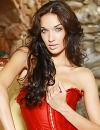 Busty brunette angel Olga M takes her red corset and black thongs off outdoors for the camera.
