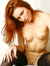 Classy redhead model Angelina A takes off her sexy lingerie and teases in black stockings.