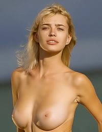 Big breasted blonde model Vika R strips on the beach and shows us her massive big hooters.
