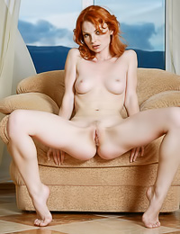 Beautiful and sexy redhead Natalia A strips on the sofa and shows us her massive hooters.