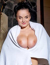 Huge breasted brunette lady Lana I takes off her bath robe and unveils her massive big jugs.