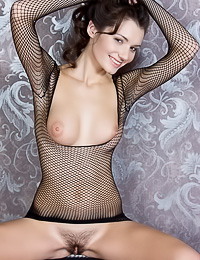 Kinky and nasty brunette babe Leila A takes her black fishnet top off and shows her fanny.