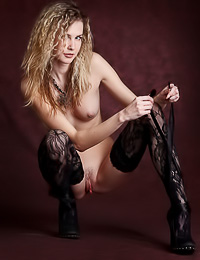 Passionate blonde honey Marena A poses on the high chair wearing just her black stockings.
