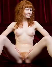 Lovely redhead chick Rochelle A takes off her red lace top and shows her perky boobs.